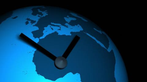 Manecillas de un reloj sobre una ilustración de la Tierra