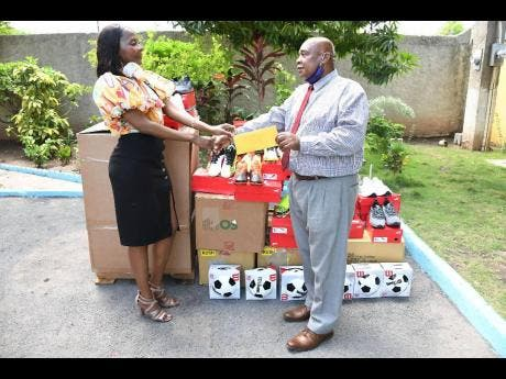Rosemary Duncan, director, Buju Banton Foundation makes the official handover to  Patrick Newman, director, Mount Olivet Boys' Home.